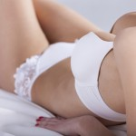 A young woman lying in white lingerie